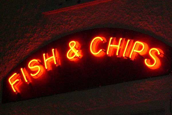 Neon fish and chip sign outdoors